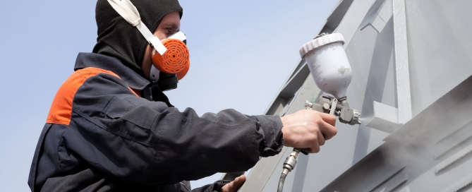 Man in mask spray painting roof trim after noticing signs it's time for exterior painting at his home